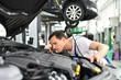 Closeup: Automechaniker kontrolliert Motor eines Fahrzeuges in der Autowerkstatt // Car mechanic inspects the engine of a vehicle in the workshop