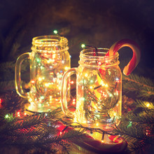 Christmas Glowing Glass Jars With Shiny Garlands And Candy Cane With Pine Branches In Darkness.