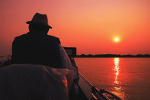 Fisherman Navigating In His Boat At Pantanal On A Golden Hour Sunset