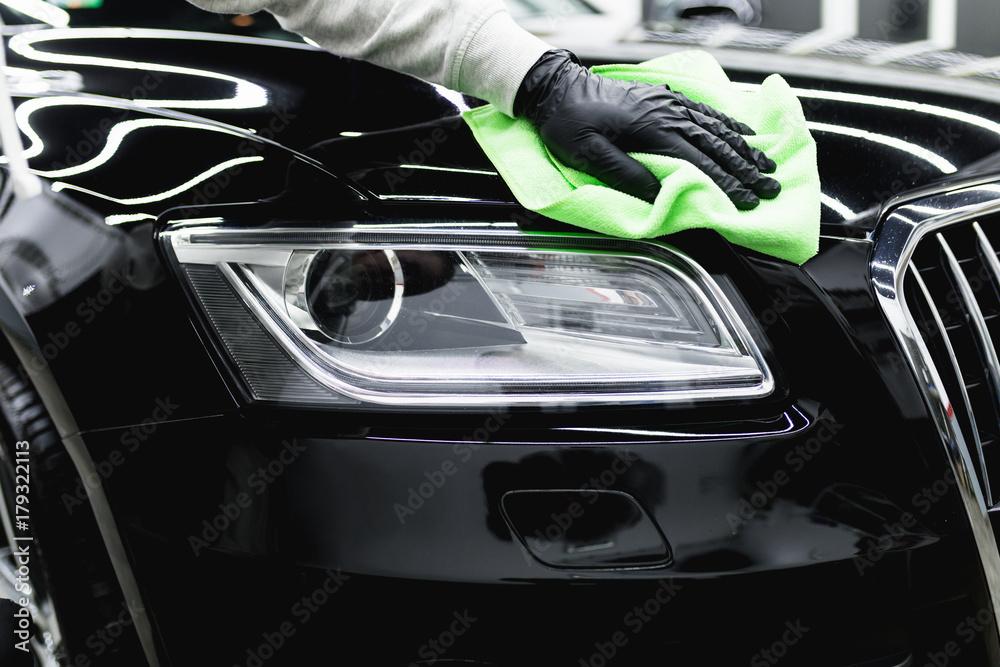 Obraz A man cleaning car with microfiber cloth, car detailing (or valeting) concept. Selective focus.  fototapeta, plakat