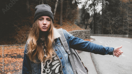 Fototapeta Young attractive Caucasian girl hitchhiking on a forest road, teen on a road tri
