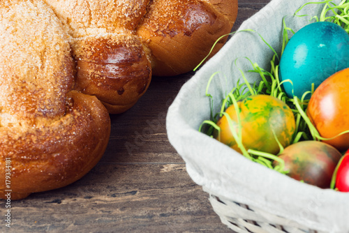 Easter wicker basket with colored eggs and Easter bread on grey wooden board.