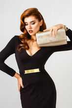 Glamour Fashion Portrait Of Elegant Beautiful Woman In Evening Black Dress With Golden Little Bag Clach. Perfact Hairstyle And Make Up. Elegant Style.