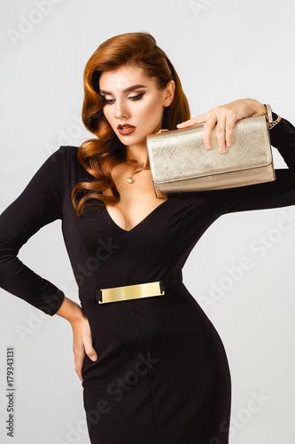 Plakat Seksowny moda piękny portret elegancka piękna kobieta w wieczór czarna sukienka z clach złoty trochę torby. Perfekcyjna fryzura i makijaż. Elegancki styl.