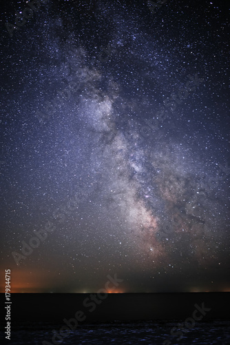 Background of bright and night-starry sky with the Milky Way upon on it and light over the water