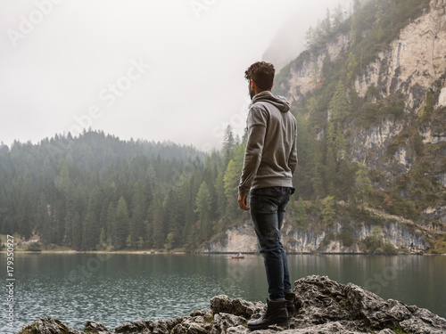 Handsome yung man standing on background of woods on shore of lake looking away Wallpaper Mural