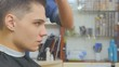 Hairdresser makes hairstyle for student in barbershop