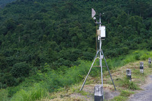 Antenna Meteorological Weather Station With Meteorology Sensors, Pale Overcast Cloudy Sky And Forest In Background. Weather Station For Background.