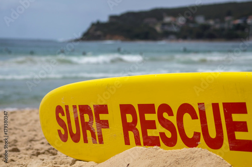 Photo Surf rescue board on Australian sandy beach with surfers in the waves on the background