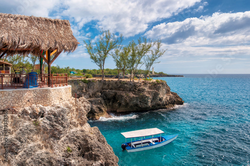 Foto op Plexiglas Caraïben Caribbean rocky beach with turquoise water, tourists boat and lighthouse in Negril, Jamaica.
