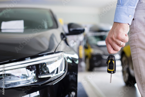 Close Up Photo Of Male Hand Holding A Car Keys Next To A Brand New