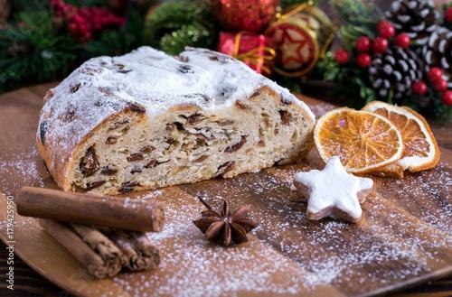Fotografía  Weihnachtlicher Butterstollen mit Rosinen auf Holztisch mit Gewürzen und Puderzu