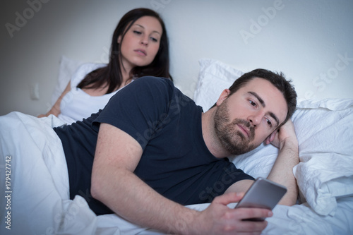 Man neglecting his girlfriend and using his mobile phone in bed Canvas Print