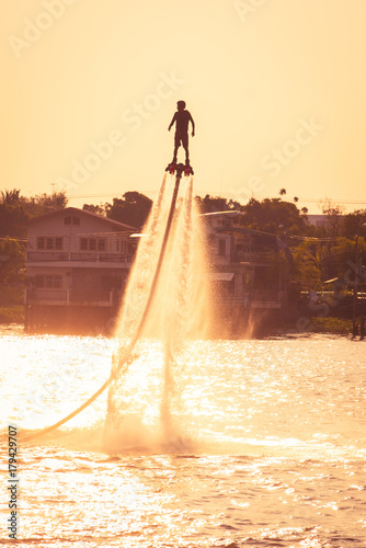 Poster Nautique motorise NONTHABURI, THAILAND - February 27 2015: Silhouette and vintage color styl of showing flyboard on Chaophya river during Chinese new year celebrations on February 27, 2015 Nonthaburi, Thailand.