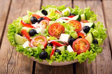 Fototapeta Do gastronomi bowl of fresh salad on a wooden table