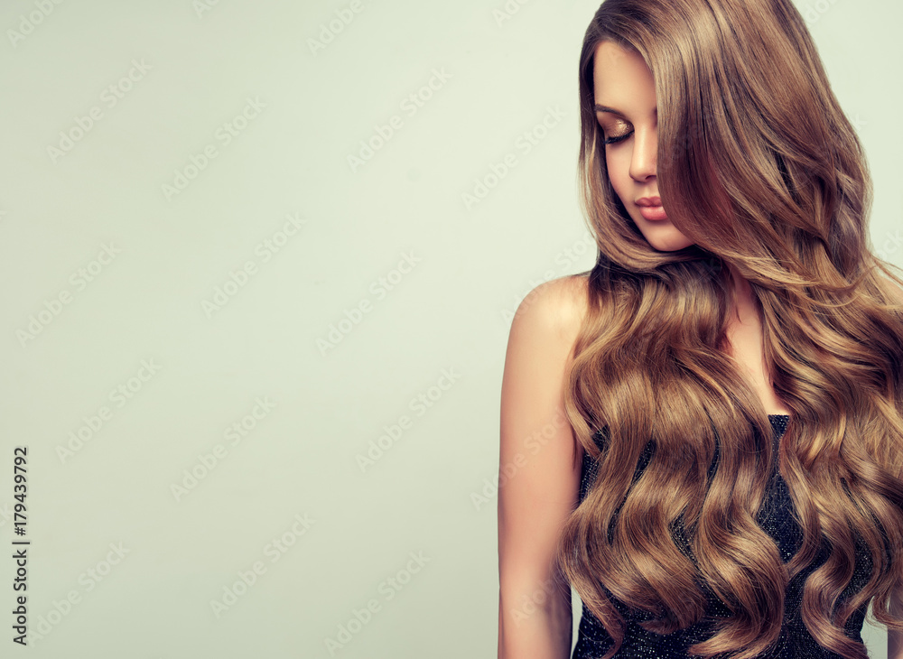 Fototapeta Brunette girl with long and volume shiny wavy hair . Beautiful woman model with curly hairstyle .