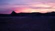 Flying over the Utah desert towards colorful sunset.
