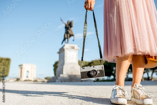 Woman holding photocamera at the famous Peyrou park in front of the Louis statue during the morning light in Montpellier city in France
