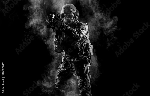 Fotografia  American soldier in combat ammunition with weapon in the hands of equipped laser