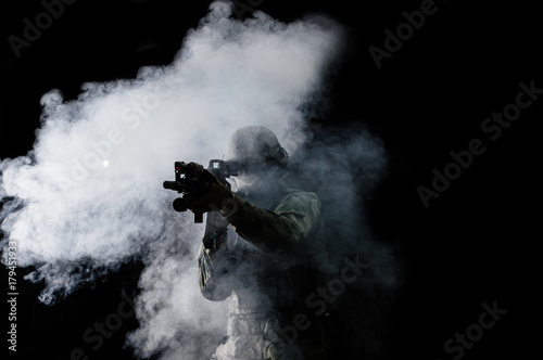 Fotomural  American soldier in combat ammunition with weapon in the hands of equipped laser sights is in battle order