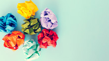 Colorful Crumpled Paper Balls On Pastel Blue Colored Background.  Copy Space, Top View