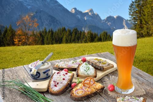 Fotografia, Obraz  Brotzeit mit einem Hefeweißbier rustikal in den bayerischen Alpen serviert -  He