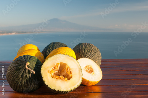 Cuadros en Lienzo Typical mediterranean fruits: yellow melon with blue sea and Mount etna in the b