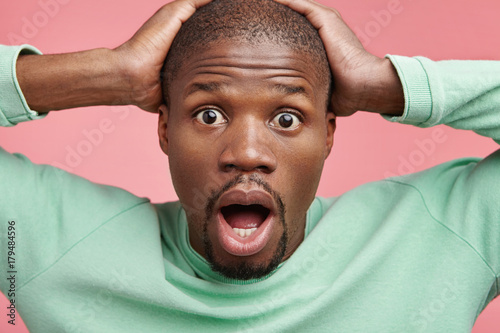 Fotografie, Obraz  Horrified dark skinned man looks with bugged eyes and widely opened mouth, terrified hearing bad news about his relatives or friends, isolated over pink background