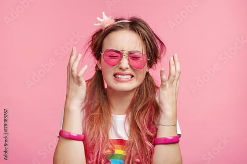 Foto op Aluminium Art Studio Emotional desperate dejected coquette woman finds out that she loose beauty contest, can`t control negative emotions, has sad and depressed expression, clenches teeth and gestures over pink wall