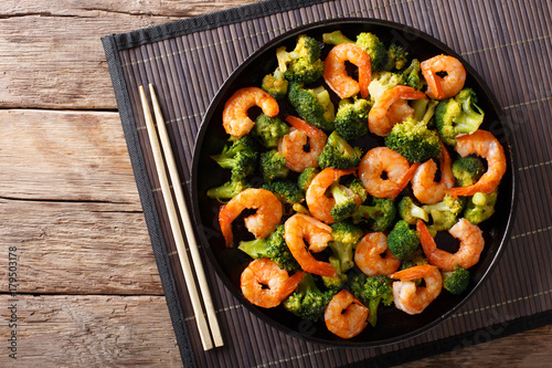 Stir frying shrimp with broccoli closeup. Horizontal top view