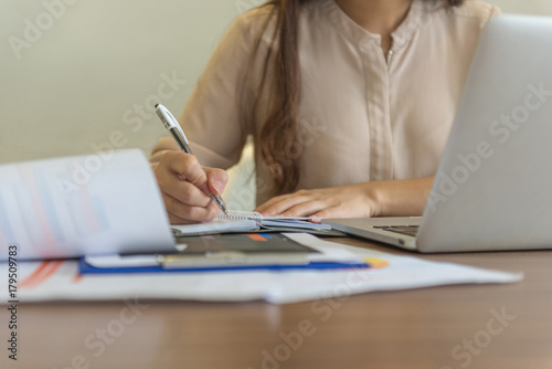 Businesswoman hand writing notes in office Wallpaper Mural
