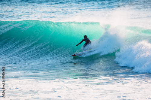 Surfer on blue wave. Winter surfing in ocean