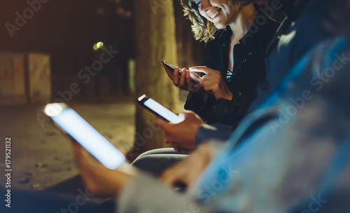 Tuinposter Restaurant People together pointing finger on screen smartphone on background bokeh light in night atmospheric city, group adult hipsters friends using in hands mobile phone, street online wi-fi internet concept