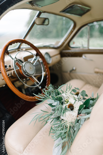 Beautiful Green Wedding Bouquet In Retro Car Wooden Steering Wheel