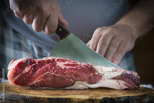 Foto op Aluminium Vlees Carnicero cortando carne de entrecot de ternera para la comida