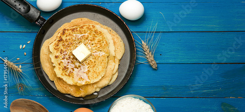 Hot delicious pancakes in frying pan on blue wooden table with flour and eggs. Pancake day background, border design panoramic banner
