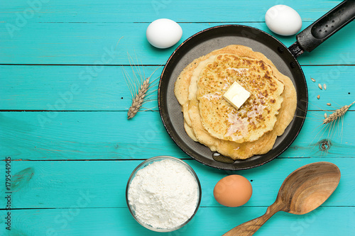 Hot delicious pancakes in frying pan on turquoise wooden table with flour and eggs. Pancake day background