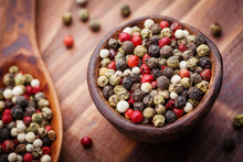 Mixed Colorful Peppercorns In Rustic Bowl On Wooden Table. Macro Shot.
