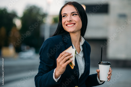 Photo Happy business woman with sandwich and coffee