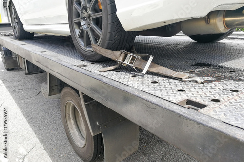 Photo  Car tire secured with safety belt on flatbed tow truck