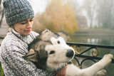 Image of young girl hug her dog, alaskan malamute, outdoor