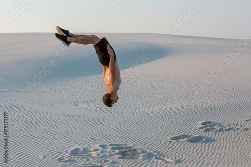 Valokuva  Man study parkour on their own. Acrobatics in the sand