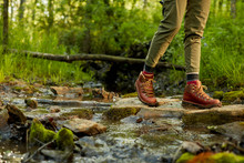 Female Hiker In Leather Boots Crossing A Stream