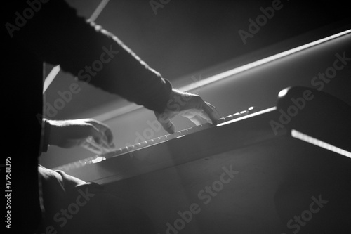 The pianist performs a musical work on the piano on stage Fotobehang