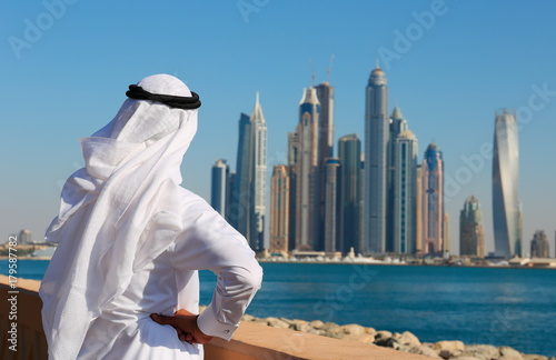 Obraz na dibondzie (fotoboard) Nowoczesne budynki w Dubai Marina. Mężczyzna w arabskiej sukience patrzy na miasto