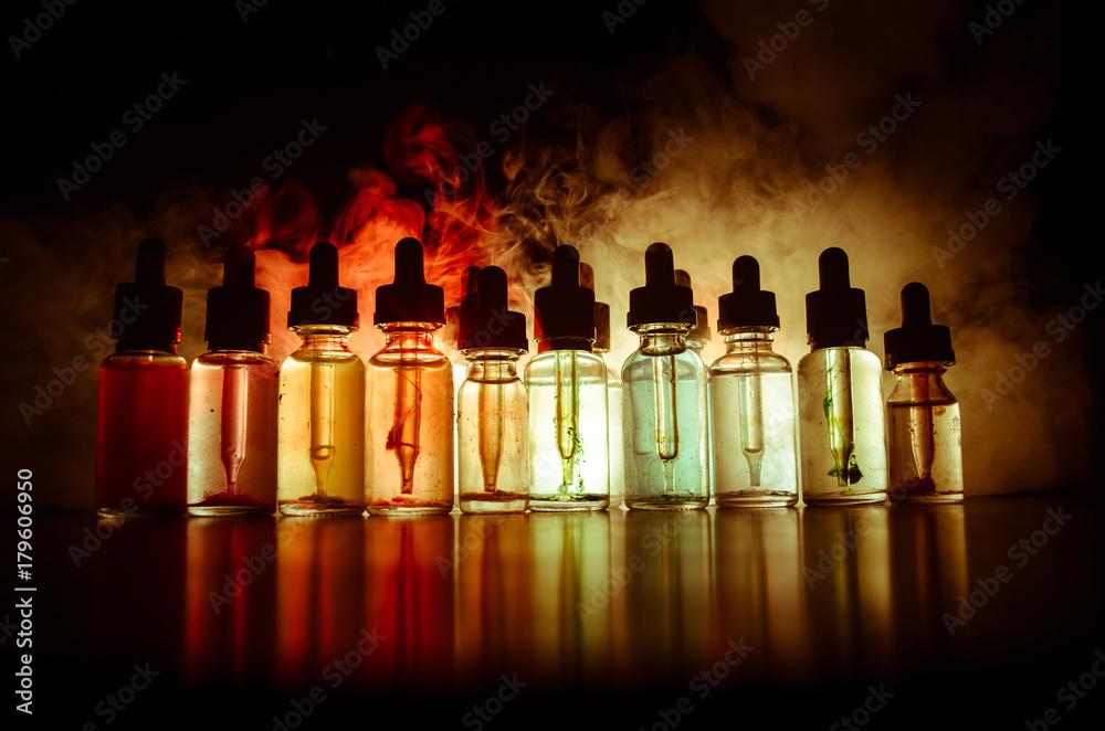 Fototapety, obrazy: Vape concept. Smoke clouds and vape liquid bottles on dark background. Light effects. Useful as background or vape advertisement or vape background. Selective focus