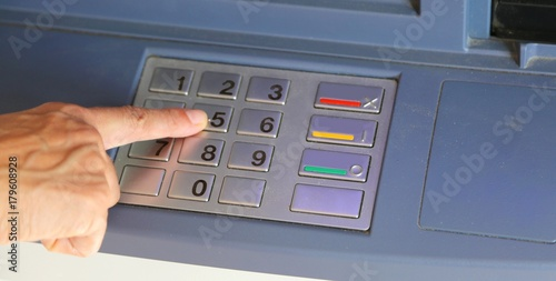woman typing the secret code on the ATM keyboard - Buy this
