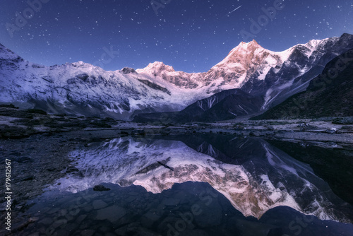 Tuinposter Reflectie Amazing night scene with himalayan mountains and mountain lake at starry night in Nepal. Landscape with high rocks with snowy peak and sky with stars reflected in water. Beautiful Manaslu, Himalayas