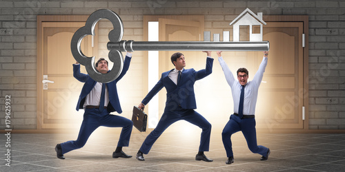 Photo Businessmen holding giant key in real estate concept