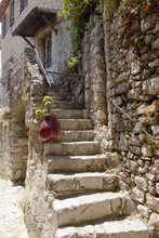 Old White Rock Staircase And Iron Fence Leading To A Home Covered In Green Vines In Eze France